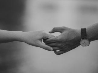 A black and white image of a couple holding hands representing common law spouses